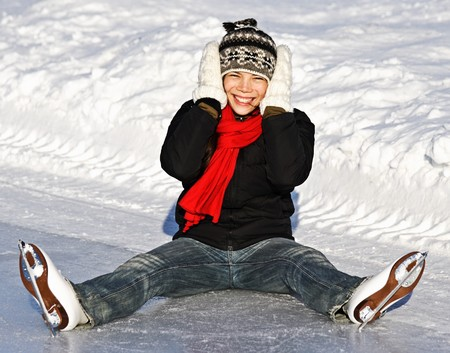 figure skater: Winter Ice skating Girl having fun on ice skate rink outdoors. Cute photo of young smiling asian woman sitting on the ice. From Quebec City, Canada. Stock Photo
