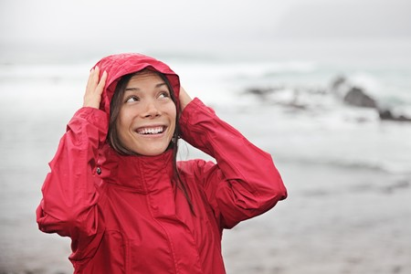 gotas de agua: Mujer sonriendo a la lluvia en impermeable rojo en la playa en un fr�o lloviendo caen d�a. Mujer del C�ucaso y de Asia.