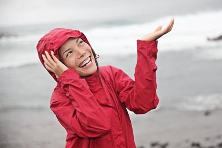 Mujer en impermeable rojo goza de la lluvia y divertirse fuera en la playa en un gris lluvioso día de otoño. Modelo de Asia y del Cáucaso.  Foto de archivo