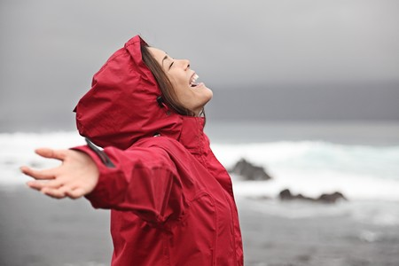 rainy season: Rain. Woman enjoying a grey rainy fall day on the beach. Young smiling woman in red raincoat. Stock Photo