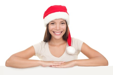Christmas woman smiling showing blank empty billboard signboard. Asian  Caucasian young female model in Santa hat isolated on white background. photo