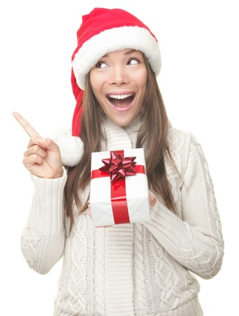Christmas woman showing copy space pointing up to the side being excited and surprised. Isolated on white background. Joyful young smiling woman in Santa hat and sweater showing empty copyspace. Asian / Caucasian female model. Stock Photo - 7869980