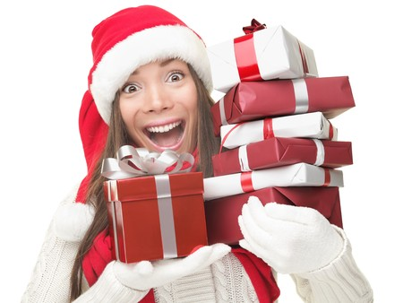 Christmas shopping woman holding gifts wearing red Santa hat. Funny santa woman portrait of a cute, beautiful smiling Asian  Caucasian model. Isolated on white background.  photo