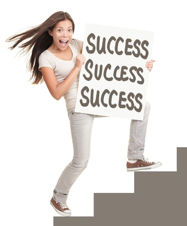 Success sign. Young successful woman showing success sign climbing stairs. Isolated on white background in full length. photo