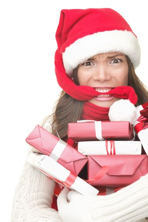 holiday spending: Christmas shopping woman stress. Young shopper holding christmas gifts  presents stressed, frustrated and angry. Funny image of Asian  caucasian woman biting her santa hat and arms full of gifts. Isolated on white background. Stock Photo