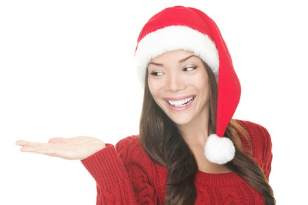 winter woman: Closeup of Christmas woman showing your product in open hand palm. Happy Young smiling woman in Santa hat and red sweater looking to the side at copy space. Portrait Asian Caucasian woman isolated on white background. Excited version also available in por