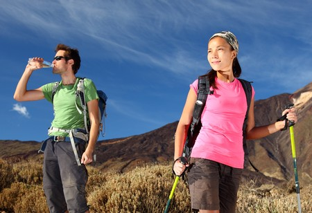 Hikers. Young couple  hiking / backpacking in very scenic and beautiful volcanic landscape on the volcano, Teide, Tenerife, Spain. Stock Photo - 8049694
