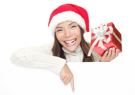 Christmas woman leaning over billboard sign. Pointing down holding gift showing big toothy smile. Caucasian  Asian woman wearing Santa hat and winter sweater isolated on white background. photo