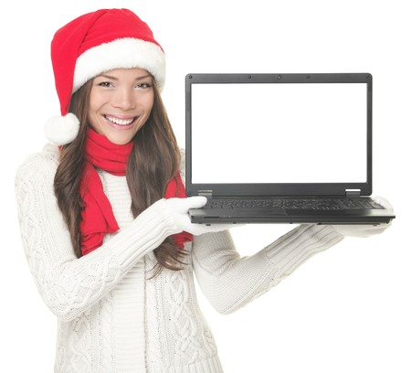 Laptop christmas girl. Smiling young woman in santa hat and sweater showing laptop. Copy space on computer screen. Caucasian Asian female model isolated on white background.  photo