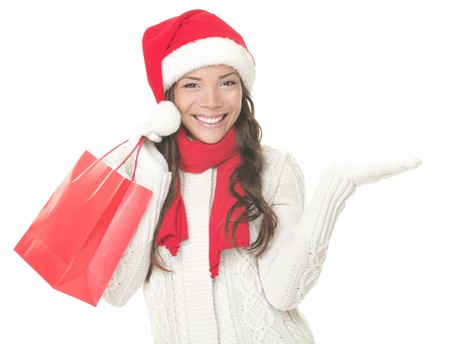 Christmas shopping woman presenting copy space. Excited santa girl showing your product or text looking sideways on copyspace with open hand palm. Closeup of mixed Asian Caucasian female model isolated on white background.  photo