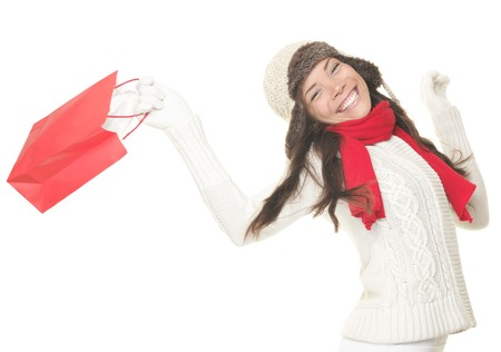 christmas shopper: Christmas shopping woman with gift bag running joyful. Smiling young woman in winter clothes holding red shopping bags. Isolated on white background. Stock Photo