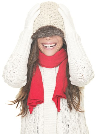 Playful cute winter woman in sweater and hat having fun laughing with winter knit hat pulled down over the eyes. Cute asian girl isolated on white background. photo