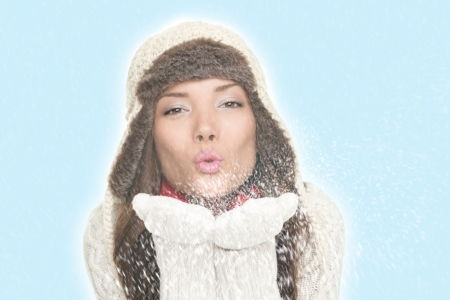 Beautiful winter woman blowing snow kiss. Isolated on blue background. Asian woman. photo