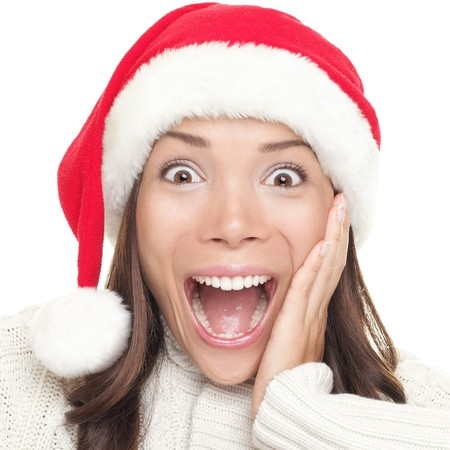expressive face: Christmas santa woman surprised. Beautiful face of happy asian woman in santa hat. Stock Photo