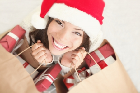 christmas girl: Woman shopping for christmas gifts. Young asian caucasian girl looking up smiling with shopping bags and santa hat. Copy space on the side. Stock Photo