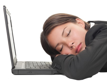 Woman sleeping on laptop taking a power nap during work. Isolated on white background. Stock Photo