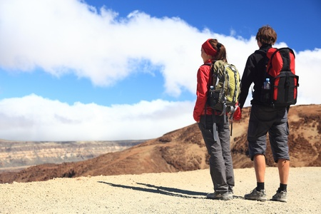 Hiking couple looking at the view holding hands in Teide National Park, Tenerife -  Copy space. Image from the volcano on the hiking path to Montana Blanca. photo