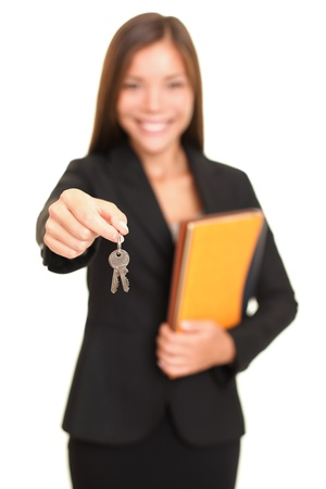 handing: Real estate agent giving keys. Young woman smiling handing over house keys to the new house owner, focus on keys. Isolated on white background.