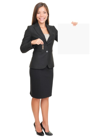 Real estate agent showing blank sign while holding house keys. Beautiful smiling woman (mixed Caucasian  Asian) isolated on white background in full body. photo