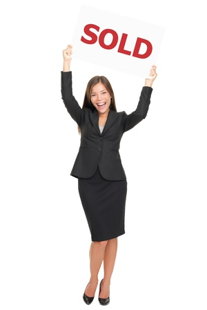 woman showing sold sign happy and excited. Smiling joyful Asian  Caucasian real estate agent woman celebrating a house sale. Isolated on white background standing in full length photo