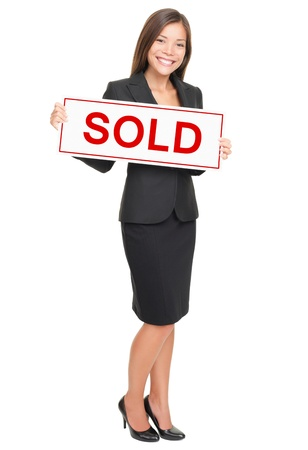 sold isolated: Real estate agent showing sold sign isolated on white background. Beautiful smiling Asian  Caucasian female realtor standing confident in full length.