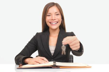 Real estate agent sitting at desk giving house keys smiling to new home owners. photo