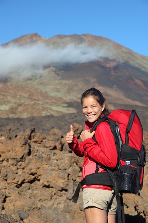 Healthy lifestyle concept- happy woman hiker giving thumbs up before the summit hike. Beautiful young Asian  Caucasian model. Image shows Pico Viejo from Teide National Park, Tenerife in the background with lots of copyspace. photo