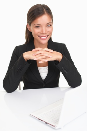 Woman sitting at desk with computer smiling at camera. Beautiful young business woman (mixed Asian Chinese  white Caucasian). photo