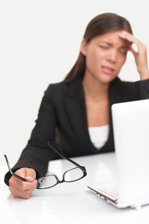 agotado: Dolor de cabeza y el estr�s en el trabajo. Joven profesional destac� y cansados con dolor de cabeza sentado en el escritorio de la Oficina. Profundidad de campo, centrarse en gafas.