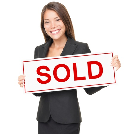 Real estate agent holding sold sign isolated on white background photo