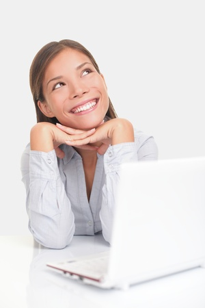 daydreaming: Woman thinking happy looking up at copy space while sitting at desk in front of laptop. Stock Photo