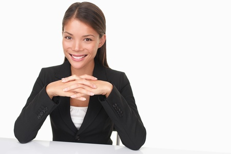 spokesperson: Woman sitting at table smiling at camera. Beautiful young businesswoman (mixed Asian Chinese  white Caucasian).