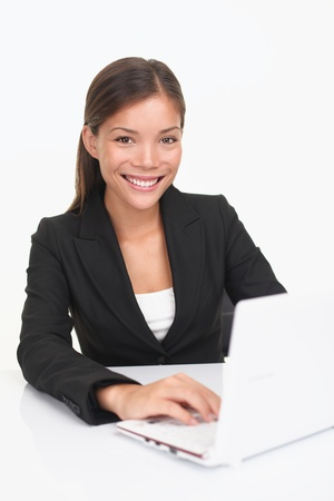 Laptop woman smiling looking at camera. Young happy businesswoman sitting at table with computer. Asian  Caucasian model. photo