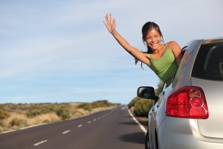 Woman in car road trip waving out the window smiling.  Image from Teide, Tenerife. Mixed race Asian  Caucasian woman. photo