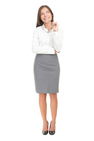 up skirt: Thinking woman in white shirt happy pensive looking up at copy space. Isolated over white background. Mixed race Caucasian white  Chinese Asian. Stock Photo