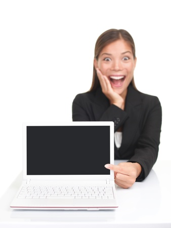 looking at computer screen: Laptop woman pointing excited at netbook screen with blank copy space. Isolated over white background. Stock Photo