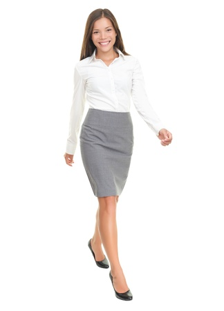 businesswoman skirt: Businesswoman walking in full length on white background. Young smiling Asian  Caucasian female business woman smiling.