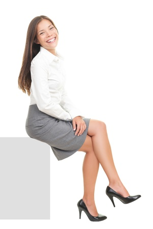 skirt suit: Businesswoman smiling sitting on blank empty billboard sign. Beautiful happy mixed race Asian  Caucasian female model isolated on white background.