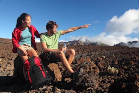 volcanic landscape: Young couple outdoors hikers looking at view pointing at copy space. Mixed race couple (asian and caucasian) on hiking trip in volcanic landscape, Teide, Tenerife, Canary Islands, Spain.