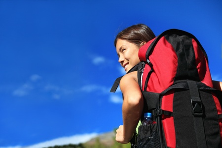 trekker: Hiker looking while backpacking  hikiking in nature. Copy space on blue sky.  Stock Photo