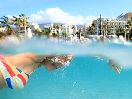 Swimmer. Woman swimming crawl in pool outside on tropical holiday resort.  photo