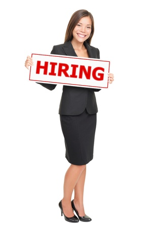 employing: Hiring job woman holding hiring sign. Young attractive smiling Caucasian  Asian businesswoman isolated on white background.