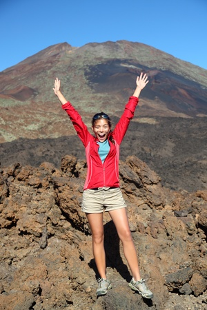 conquered: Portrait of happy hiker with arms raised in air with conquered mountain behind. Mountain volcano Pico Viejo on Teide, Tenerife, Canary Islands, Spain.