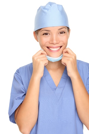 Young female nurse with surgeon mask and scrub smiling happy. Isolated on white background. Mixed race Asian Caucasian female model. Stock Photo - 8548817
