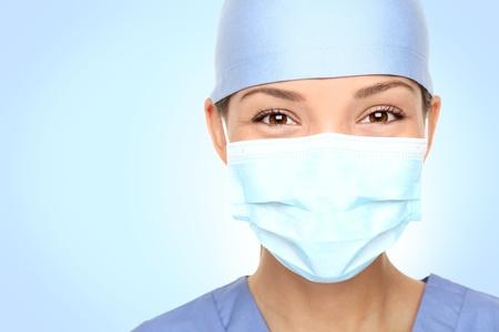 quirurgico: Doctor  enfermera sonriendo detr�s de la m�scara de cirujano. Closeup retrato de joven cauc�sica asi�ticos modelo azul matorrales m�dica.