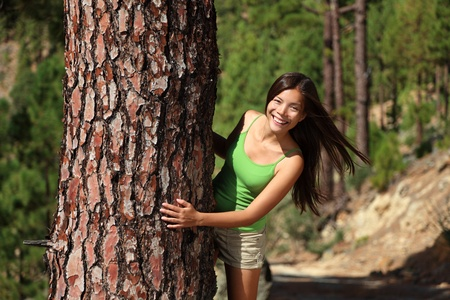 hide and seek: Fresh beautiful smiling woman in summer forest playful. Image from pine tree forest near Vilaflor, Tenerife, Canary Islands. Stock Photo