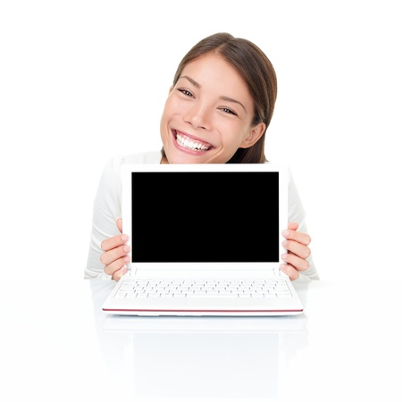 Woman showing netbook laptop screen copy space while sitting by white table. Asian Caucasian female model isolated on white background. photo