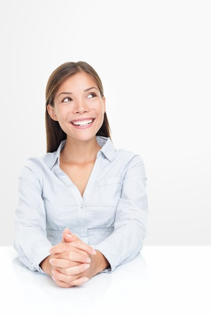 Woman smiling looking up thinking sitting at table. Positive, optimistic and friendly looking Asian  Caucasian businesswoman isolated on white background. photo
