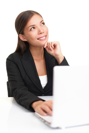 Businesswoman on laptop thinking looking up at copy space. Beautiful young business woman sitting by table isolated on white background. photo