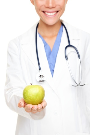Doctor woman giving  showing apple. Young female medical professional isolated on white background. photo